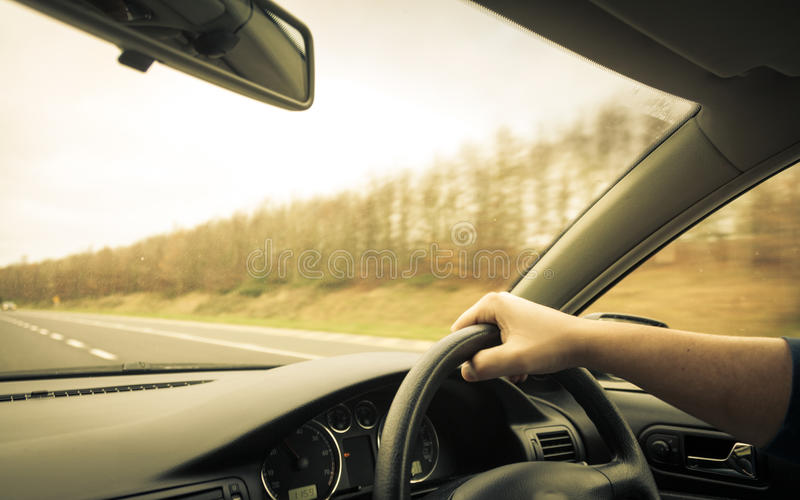 Male driver hands on steering wheel of a car and road. Male driver hands holding steering wheel of a car and road stock photography