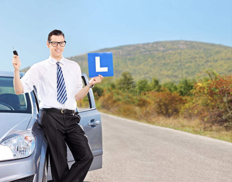Male driver holding l sign on an open road. Male driver holding l sign and a car key on an open road shot with tilt and shift lens royalty free stock image