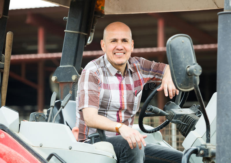 Male driver operating modern tractor. In livestock farm royalty free stock photography