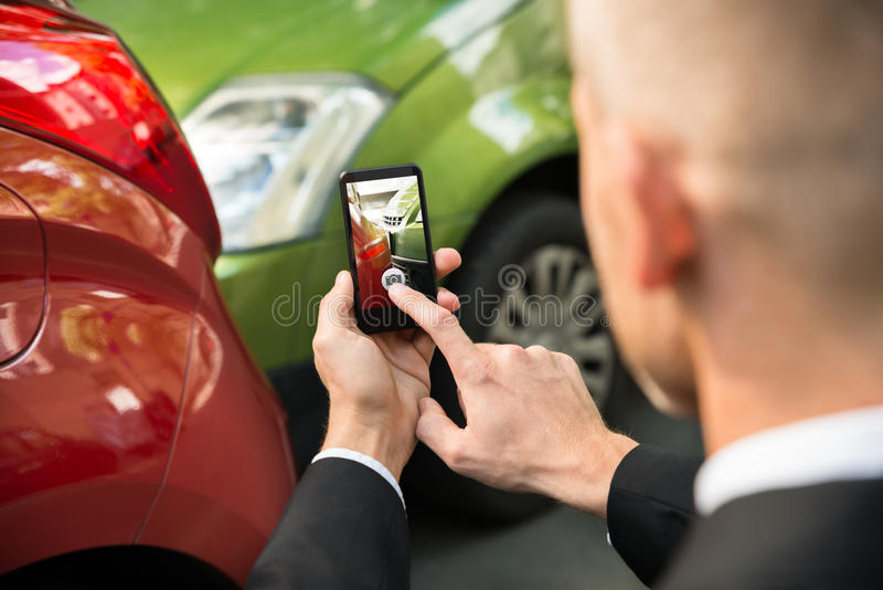 Male driver photographing of damaged car. Male Driver Photographing With His Cellphone After Traffic Collision stock image