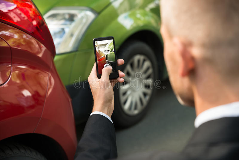 Male driver photographing of damaged car. Male Driver Photographing With His Cellphone After Traffic Collision royalty free stock images