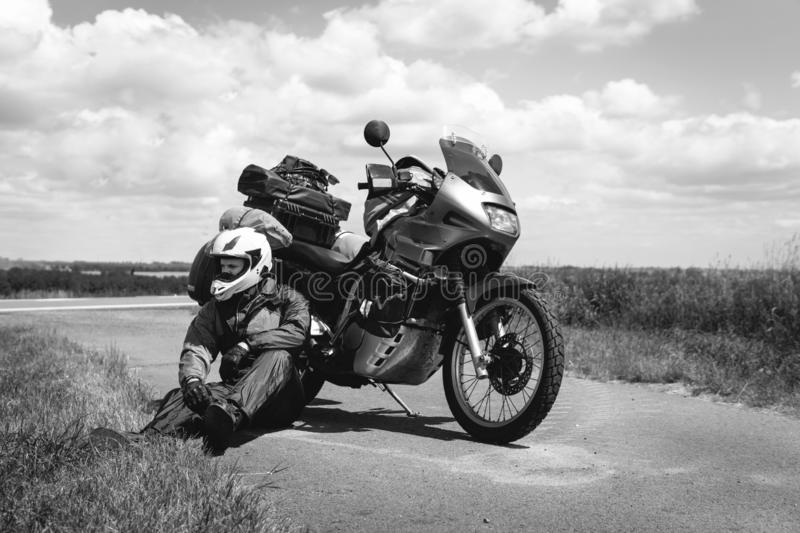 A male driver in a raincoat is sitting by adventure motorbike with side bags. a motorcycle tour journey. Outdoor road summer time. Black and white, bw, freedom royalty free stock images