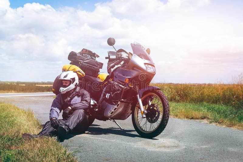 A male driver in a raincoat is sitting by adventure motorbike with side bags. a motorcycle tour journey. Outdoor road summer time. Light warm tinting, glow royalty free stock image