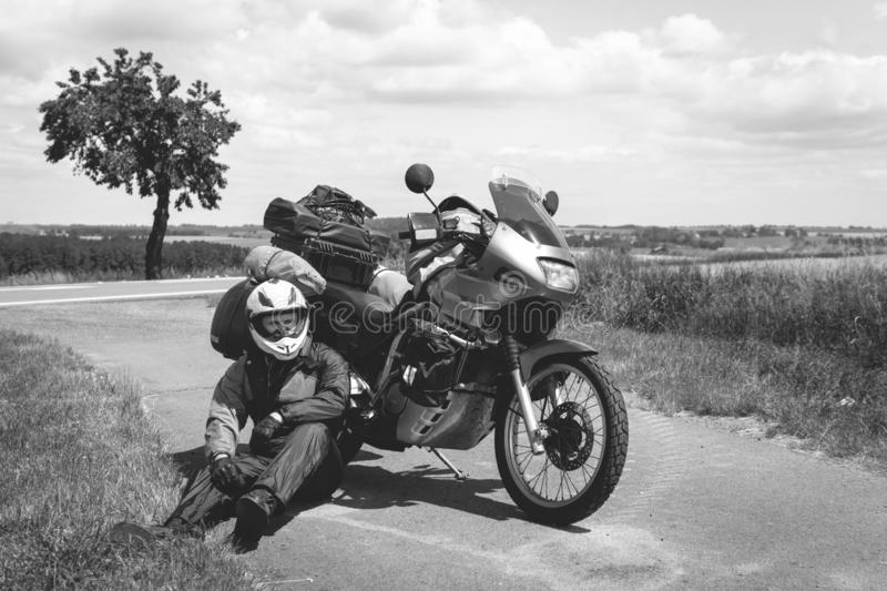A male driver in a raincoat is sitting by adventure motorbike with side bags. a motorcycle tour journey. Outdoor road summer time. World travel on two wheels royalty free stock image
