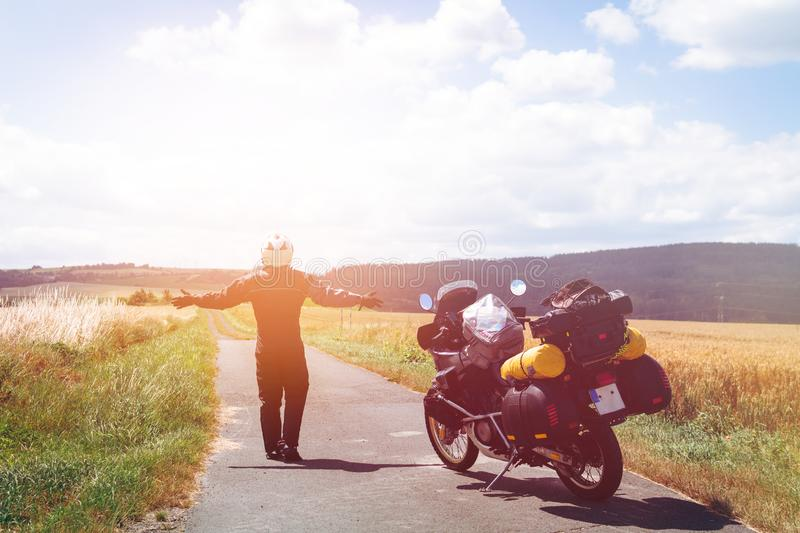 A male driver in a raincoat is standing by adventure motorbike his arms outstretched. a motorcycle tour journey. Outdoor, field. And sky. light warm tinting stock photo