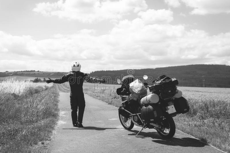 A male driver in a raincoat is standing by adventure motorbike his arms outstretched. a motorcycle tour journey. Outdoor, field. And sky. black and white, bw royalty free stock photo