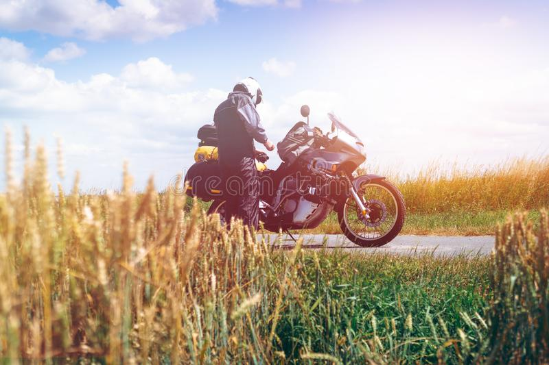 A male driver in a raincoat is standing by adventure motorbike with side bags. a motorcycle tour journey. Outdoor. light warm royalty free stock photos