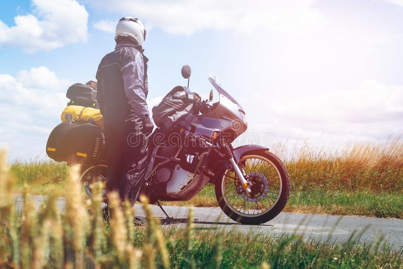 A male driver in a raincoat is standing by adventure motorbike with side bags. a motorcycle tour journey. Outdoor. light warm. Tinting, glow, freedom concept stock photography