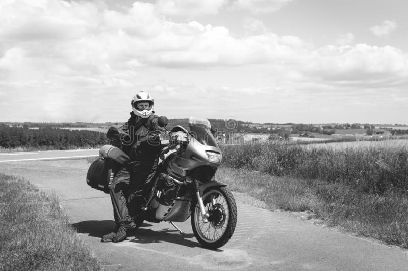 A male driver in a raincoat is standing by adventure motorbike with side bags. a motorcycle tour journey. Outdoor. World travel. Black and white, bw, freedom stock images