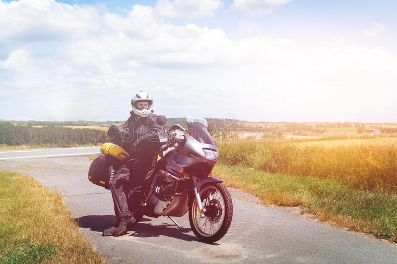 A male driver in a raincoat is standing by adventure motorbike with side bags. a motorcycle tour journey. Outdoor. World travel on royalty free stock image