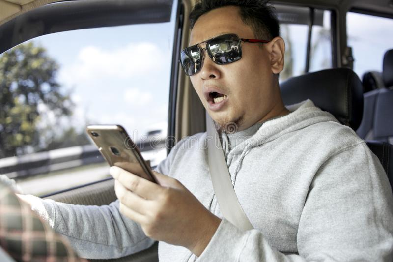 Male Driver Reading Message on  Smart Phone While Driving a Car. Male Asian driver reading message on smart phone while driving a car royalty free stock images