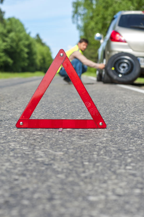 Male driver in reflective vest changing the tire stock photo