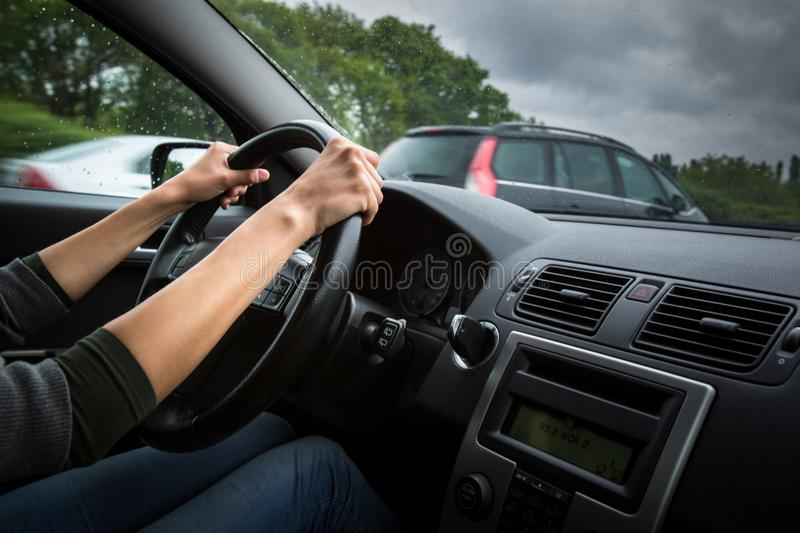 Male driver`s hands driving a car on a highway. Color toned image; shallow DOF stock image