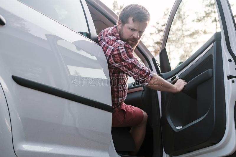 A male driver sits behind the wheel of a car with an open door and looks back at problems with the wheel of the car. A male driver sits behind the wheel of a stock photos