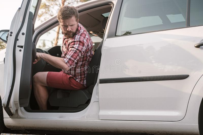 A male driver sits behind the wheel of a car with an open door and looks back at problems with the wheel of the car. A male driver sits behind the wheel of a stock images