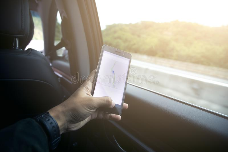 Male driver sitting in the car and holding black mobile smart phone with map gps navigation application. With planned route on the screen royalty free stock photography