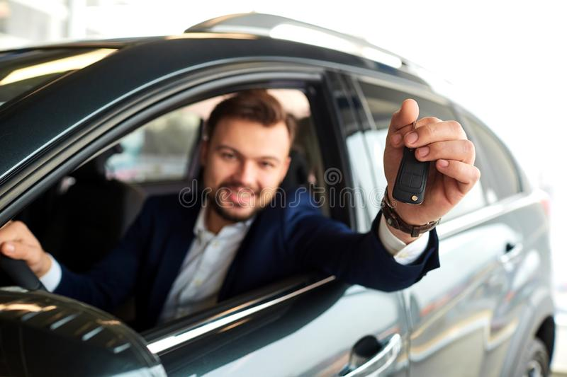 Male driver smiling holds the keys to the car. In the showroom stock images