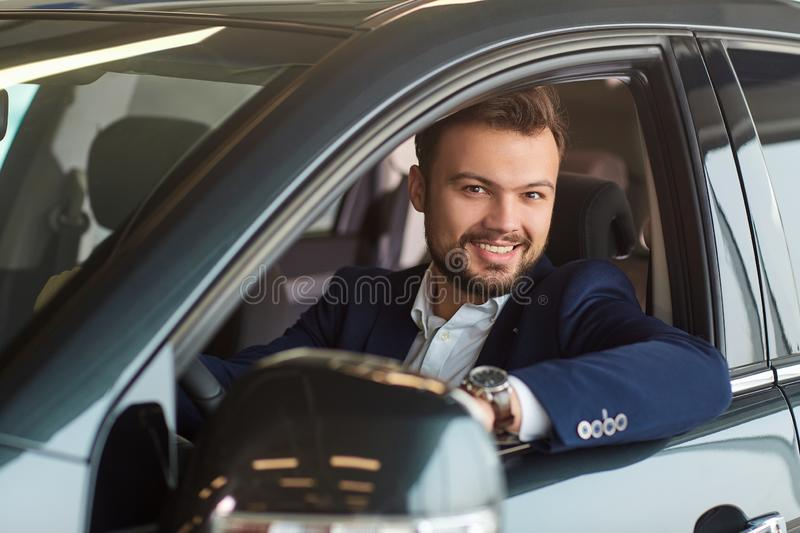 Male driver smiling to the car. In the showroom stock photos