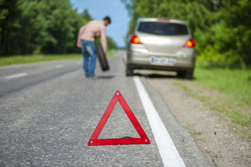 Male driver with spare wheel after breakdown. On the roadside. Focus on red triangle warning sign stock photography