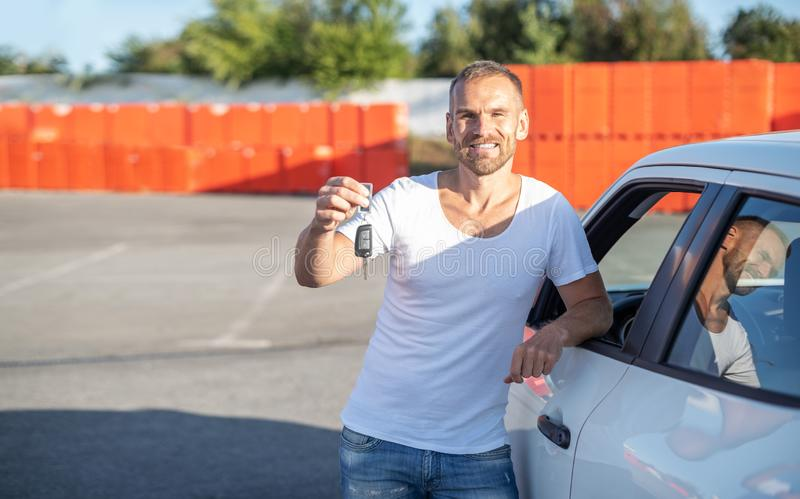 A male driver stands near a car with a key in his hand and smiles. A male driver stands near a white car with a key in his hand and smiles stock images
