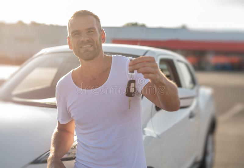 A male driver stands near a car with a key in his hand and smiles. A male driver stands near a white car with a key in his hand and smiles stock photo