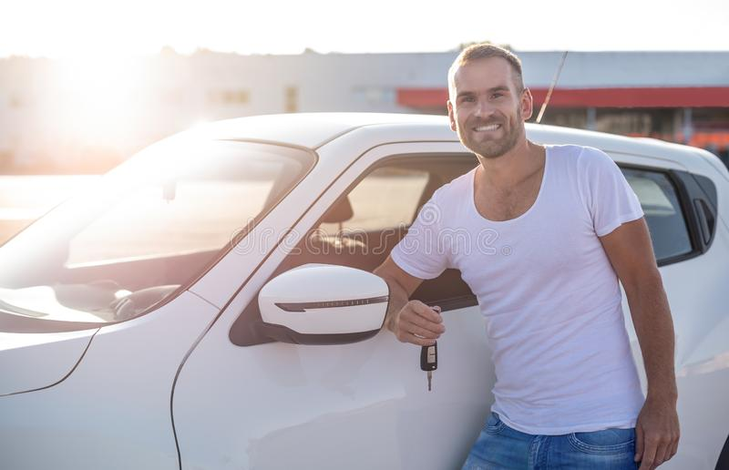 A male driver stands near a car with a key in his hand and smiles. A male driver stands near a white car with a key in his hand and smiles royalty free stock photo
