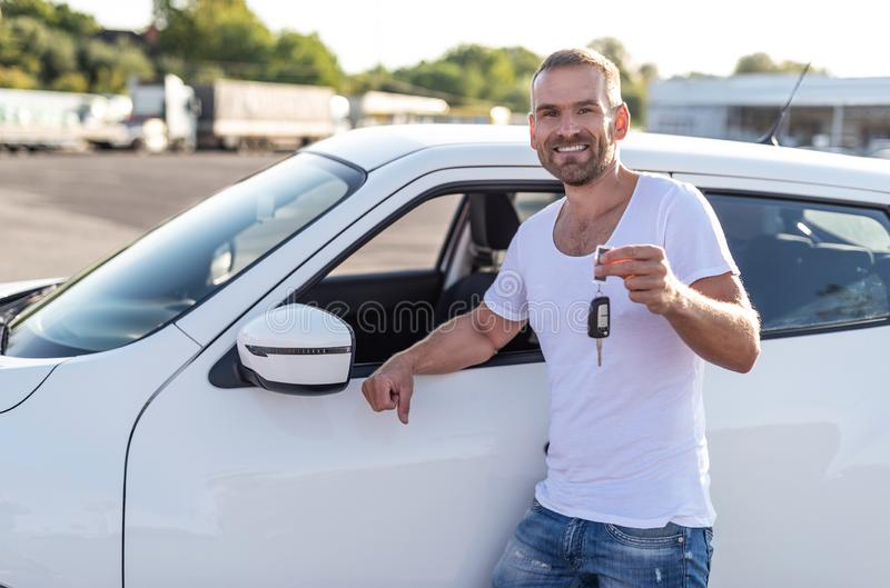 A male driver stands near a car with a key in his hand and smiles. A male driver stands near a white car with a key in his hand and smiles royalty free stock images