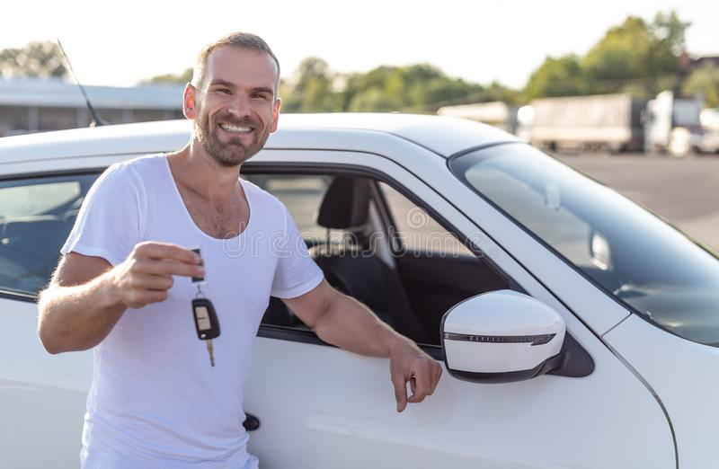 A male driver stands near a car with a key in his hand and smiles. A male driver stands near a white car with a key in his hand and smiles royalty free stock image
