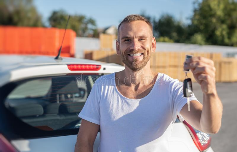 A male driver stands near a car with a key in his hand and smiles. A male driver stands near a white car with a key in his hand and smiles. Buying or renting a stock photo