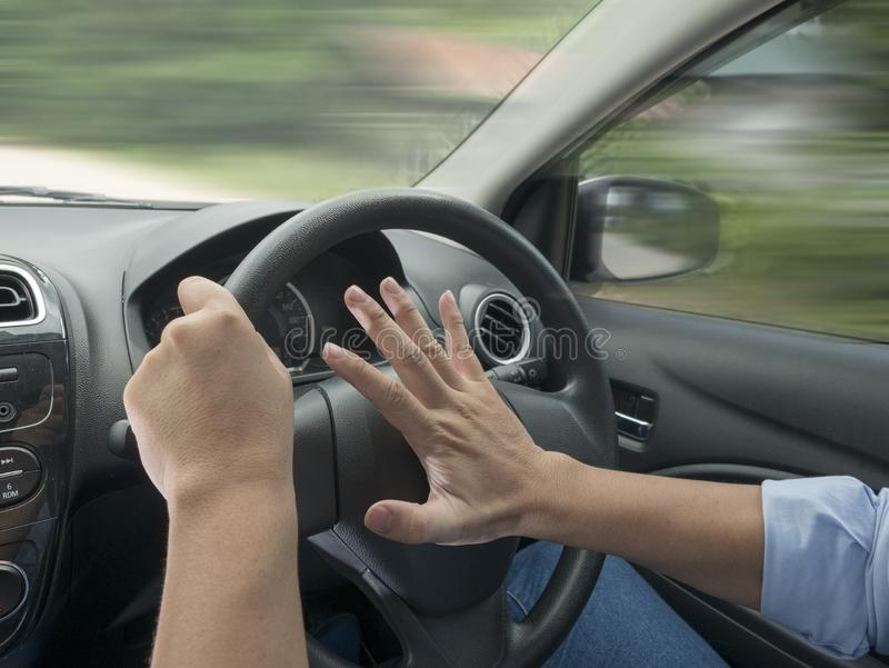 Driver Pressing Car Horn. Male driver steering a car and press car horn, honking soung to warn other people in traffic stock image