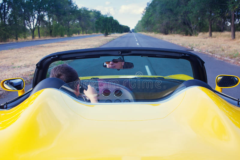 Male driver steering convertible car. With open roof. Back view stock image