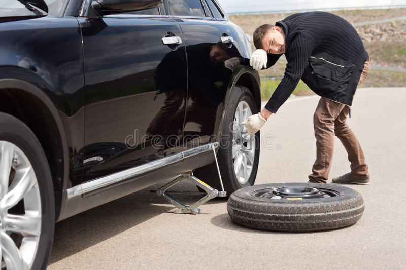 Male driver struggling to change his car tyre. Resting his head against the side of the vehicle as he tries to loosen the wheel nuts with a spanner royalty free stock photography