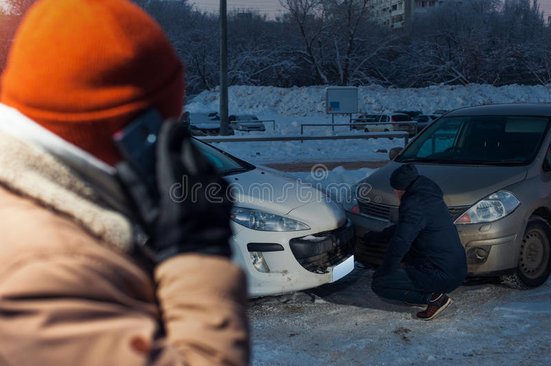 Male driver talking on the phone after car crash. Male driver talking on the phone after car accident. Two men examining damaged auto. Car collision stock photography