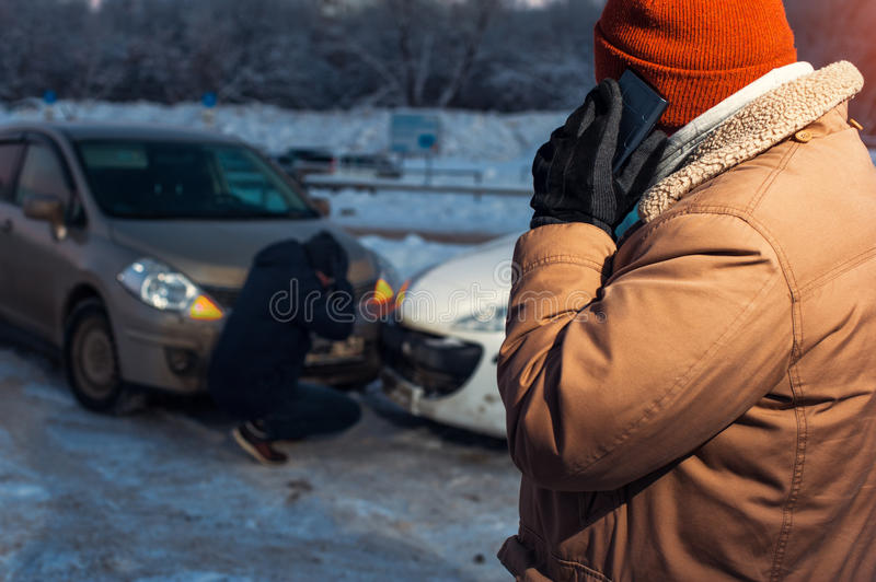 Male driver talking on the phone after car crash. Two upset men after accident on winter city road royalty free stock image
