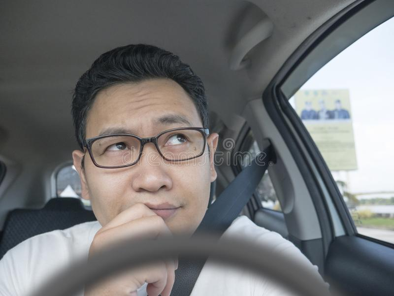 Male Driver With Thinking Gesture. Portrait of young Asian male driver thinking something, friendly ride car sharing driver waiting for client online pooling stock photography