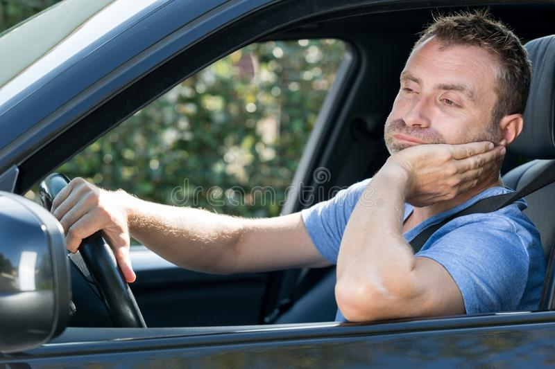 Male driver at wheel sighing in frustration. Male driver at the wheel sighing in frustration stock image