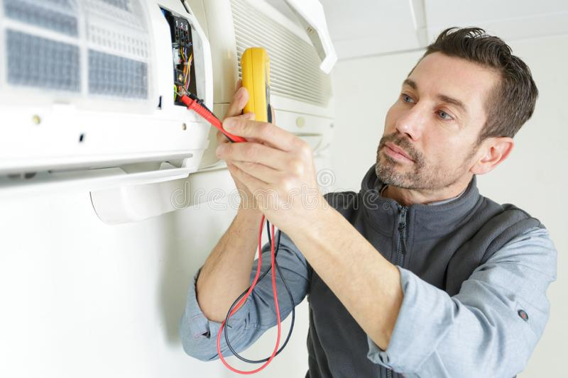 Male electrician checking air conditioner with digital multimeter stock images