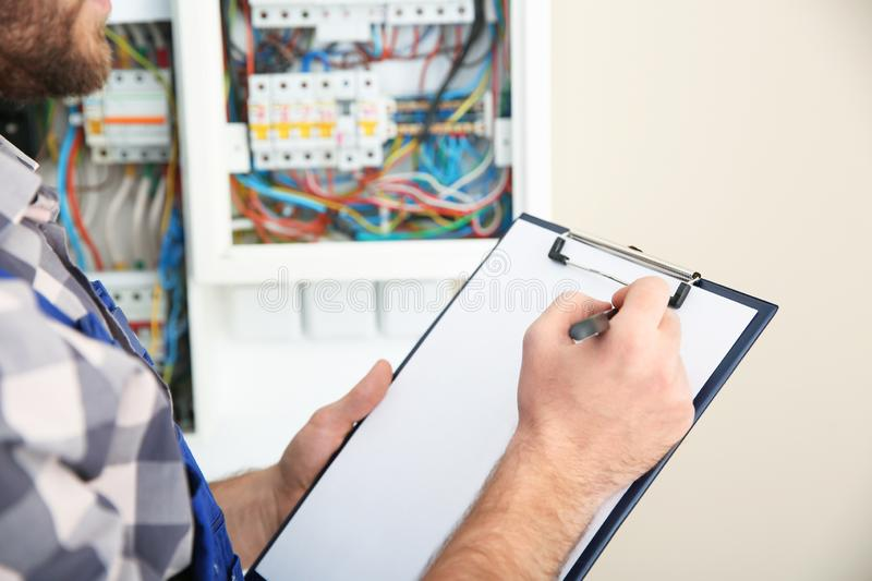 Male electrician with clipboard near fuse board indoors royalty free stock photo