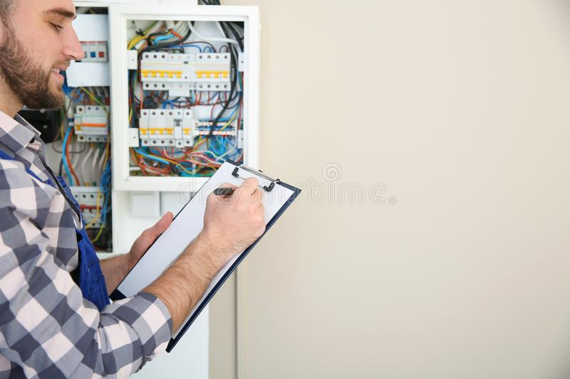 Male electrician with clipboard near fuse board indoors stock photo