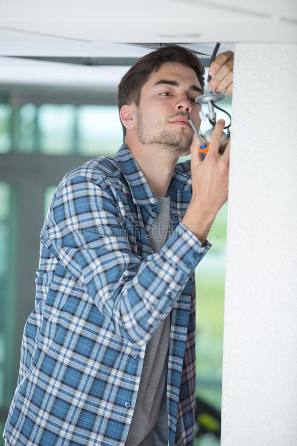 Male electrician fixing light on ceiling with screwdriver royalty free stock images