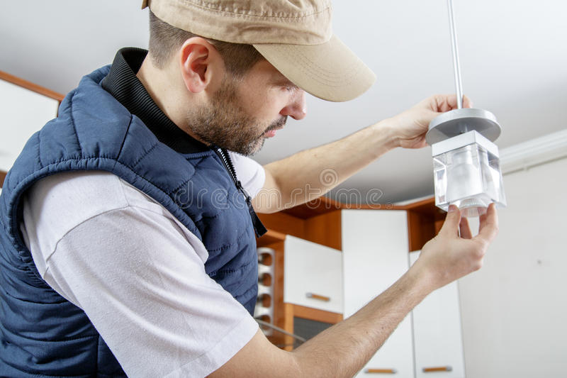 A male electrician fixing light on the ceiling. stock images