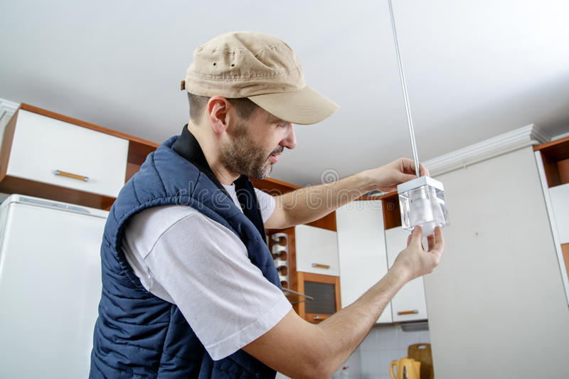 A male electrician fixing light on the ceiling. Worker changing a light bulb in the kitchen. Close-up royalty free stock photography