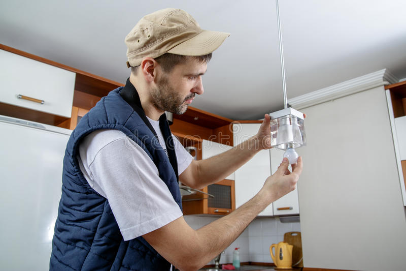 A male electrician fixing light on the ceiling. stock photos