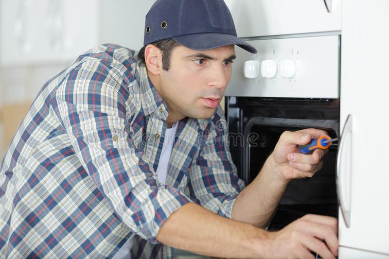 Male electrician fixing oven in kitchen royalty free stock photo