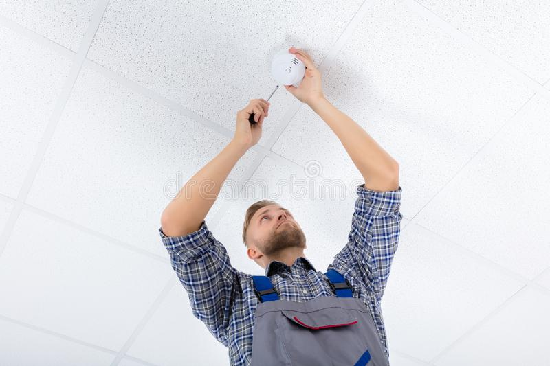 Male Electrician Fixing Smoke Detector. Low Angle View Of A Male Electrician Fixing Smoke Detector Using Screwdriver On Ceiling Wall royalty free stock photos
