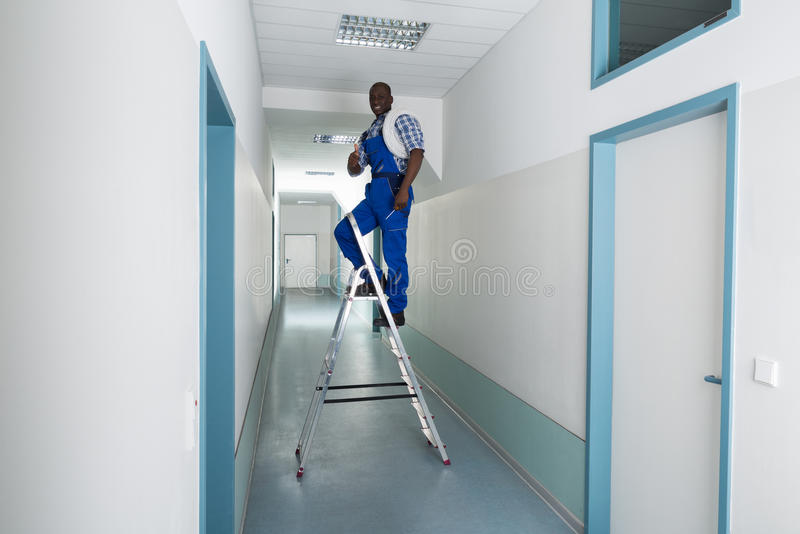 Male Electrician Gesturing Thumbs Up. Young African Male Electrician On Stepladder Gesturing Thumbs Up Sign stock photo