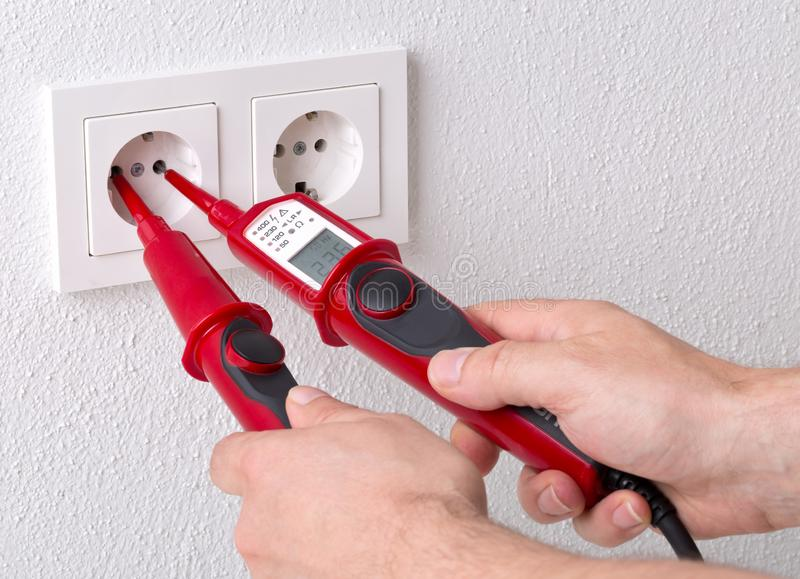 Male electrician measuring power on wall outlet with measuring device royalty free stock image