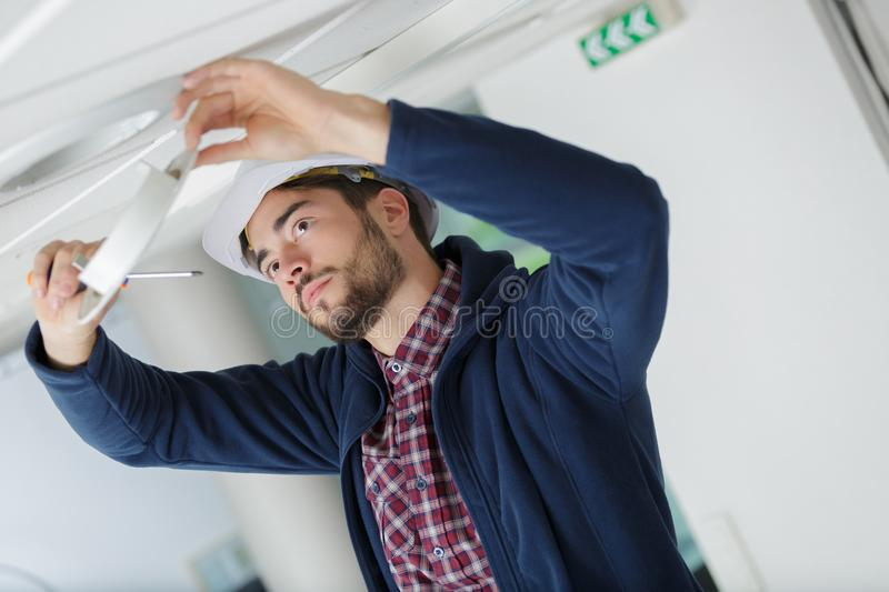 Male electrician with screwdriver repairing fire sensor royalty free stock photography