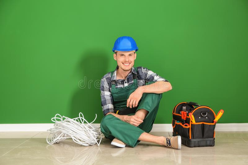Male electrician sitting on floor near color wall royalty free stock photo