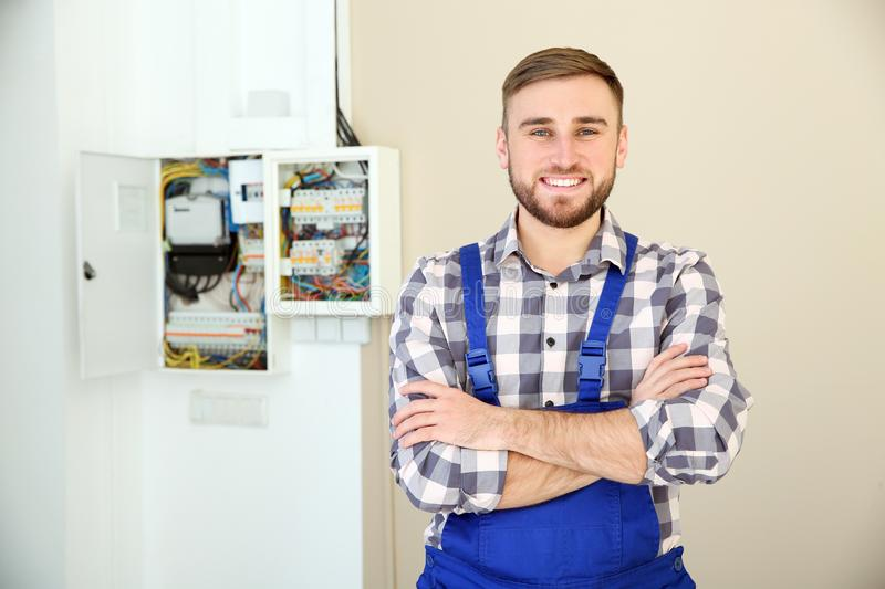 Male electrician standing near fuse board stock photography